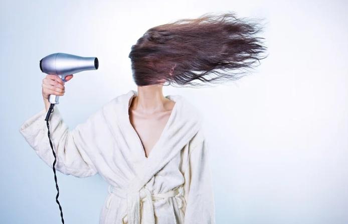 Девушка сушит феном волосы.
